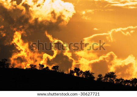 Stormy Pilanesberg landscape with omenous clouds on the horizon - stock photo