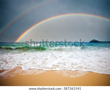 stormy sea and cloudy sky with rainbow - stock photo