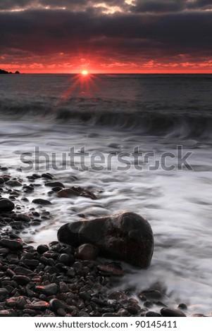 Stormy sea at sunrise - stock photo