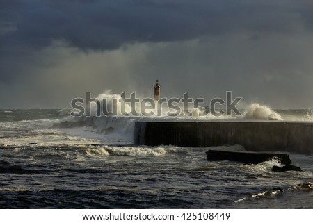 Stormy sea waves over pier and lighthouse with beautiful light before rain. Ave river mouth, Vila do Conde, north of Portugal. - stock photo
