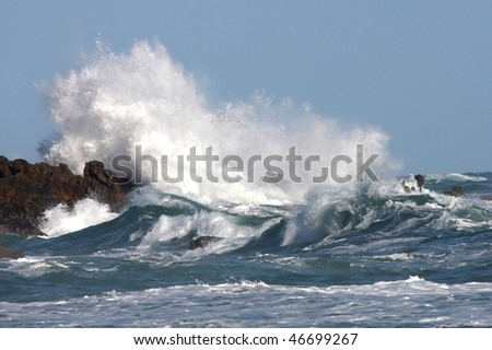 Stormy seas and crashing waves on rocks - stock photo