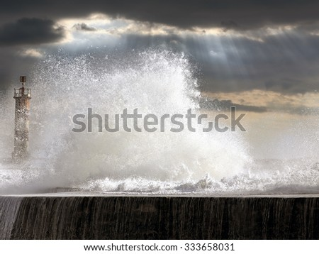 Stormy seascape at sunset with big splashing waves over pier and beacon. North of Portugal. Enhanced sky. - stock photo