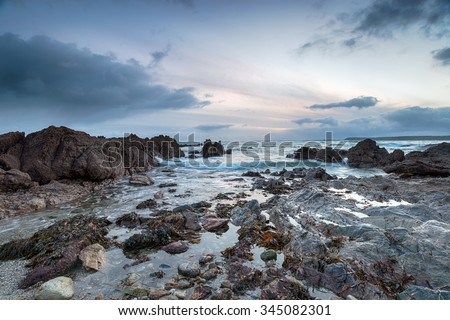 Stormy skies and rocks at low tide on Hemmick Beach on the south Cornish coast - stock photo
