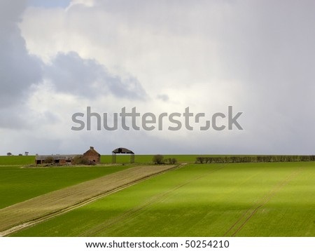 stormy skies in april over fields of fresh green young corn and an isolated derelict farm on the yorkshire wolds - stock photo