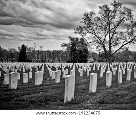 Stormy skies over a graveyard in moody black and white - stock photo
