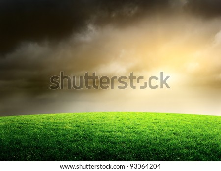 stormy sky and field of spring grass - stock photo