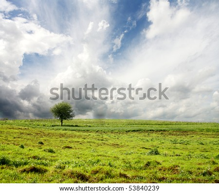 Stormy sky and green landscape - stock photo