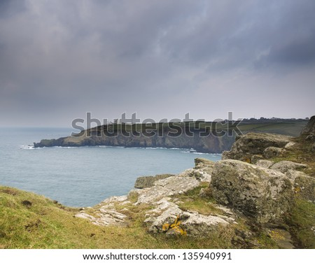 Stormy sky over headland peninsula with lighthouse - stock photo