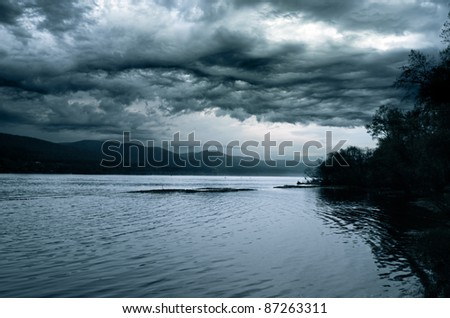 Stormy sky over the night river. - stock photo