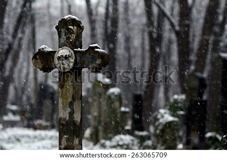 Stormy snow afternoon in a christian cemetery - stock photo