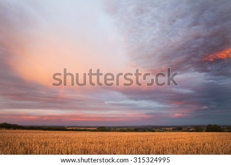 Stormy Sunset Clouds over Harvested Field - stock photo