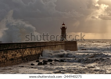 Stormy sunset with big wave over pier and sunbeams, Porto, Portugal - stock photo