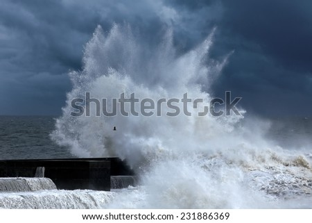 Stormy waves over a pier in the north of Portugal.Enhanced sky. - stock photo