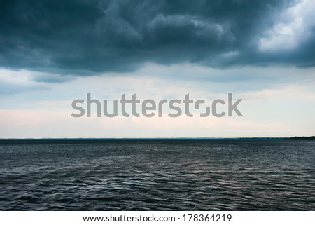 stormy weather at lake with dark clouds before storm - stock photo