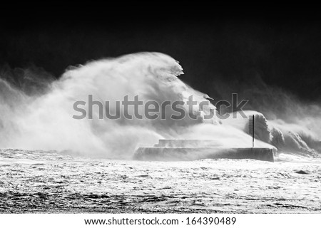 stormy weather on sea with big waves breaking on breakwater - stock photo