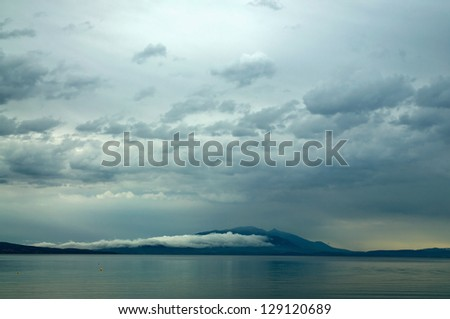stormy weather over the mountains and the  sea - stock photo