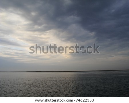 Stormy Weather Seascape - Bad weather rolls in on a lake, with waves and dark clouds. - stock photo