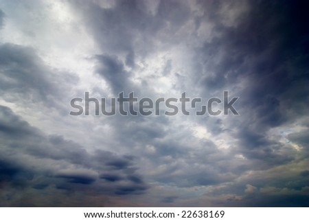 stormy weather with dark clouds in the dramatic sky - stock photo