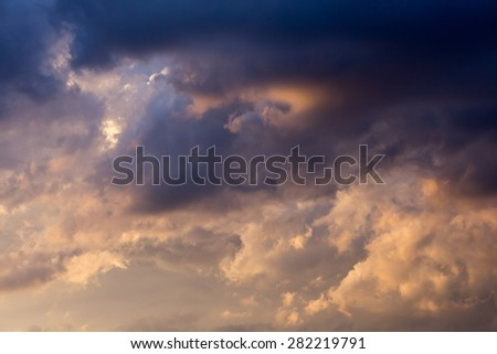 Stormy weather with dark clouds over blue sky at sunset