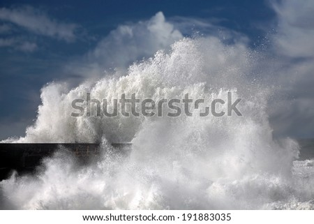 Stormy white wave over a pier in the north portuguese coast - stock photo