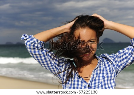stormy wind: wind blowing young woman?s hair by the sea - stock photo
