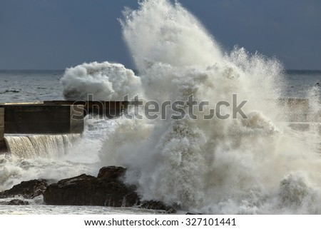 Stormy windy wave against sea dangerous rocks, pier and beacon