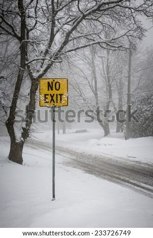 Stormy winter road and trees covered in snow with Yellow No Exit sign - stock photo