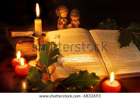 Story of christmas in an old bible, with the famous passage lit with a torch and candles - stock photo