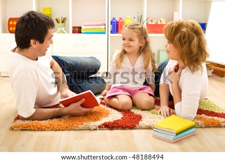 Story time - happy family with a child reading a book laying on the floor
