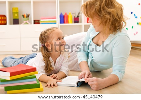 Story time with mom - little girl and woman reading laying on the floor