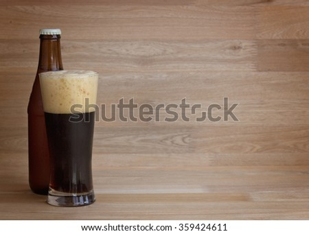 Stout beer in glass and bottle over wood