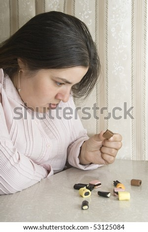 Stout woman contemplating over several sweets - stock photo