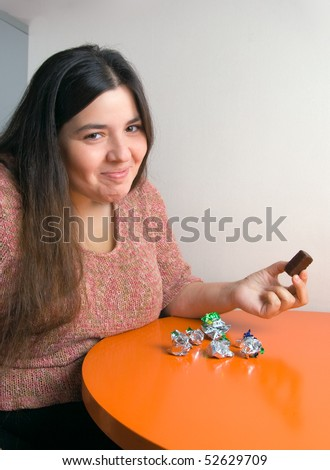 Stout woman contemplating over wrappers of sweets - stock photo
