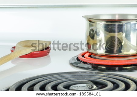 Stove top with pot & wooden spoon - stock photo
