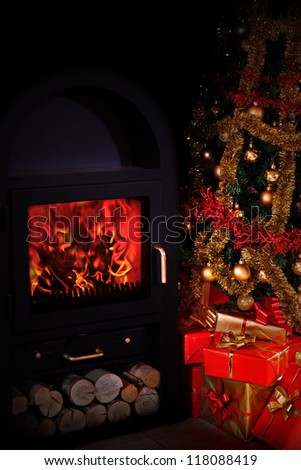 stoves illuminate the Christmas tree with gifts - stock photo