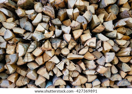 stow of firewood ,a lot of firewood outdoor, brown background, firewood stock for fuel burning - stock photo