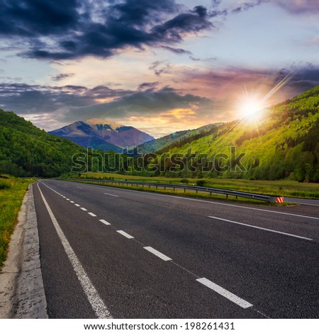straight asphalt road in mountains passes through the green shaded forest at sunset composite - stock photo
