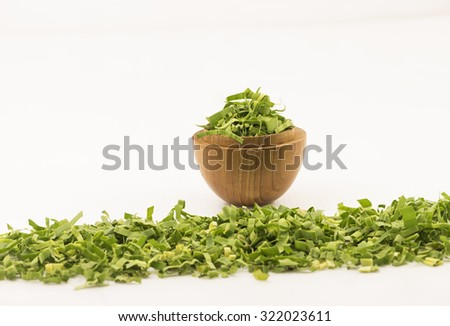 Straight closeup view on shredded pandan leaf in a wooden bowl.   Foreground with a row partially focus loose leaf. The leaf is use as herbal tea for its strong sweet fragrance and medicinal benefits. - stock photo
