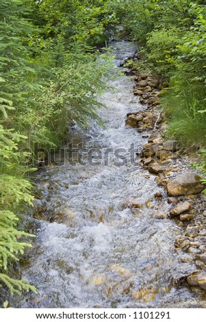 straight creek in the mountains - with a lot of brown stones - stock photo