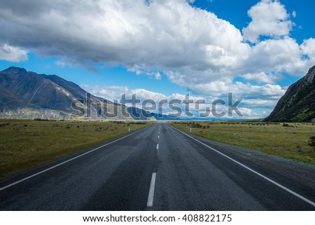 Straight empty highway leading into Aoraki-Mount Cook National Park to the highest peaks of the Southern Alps lining the horizon, South Island of New Zealand - stock photo