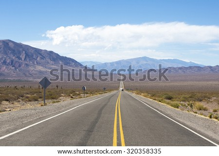 Straight Famous Route 40 with mountains, arid landscape and blue sky, on the way to Cafayate in Salta Province. Argentina - stock photo