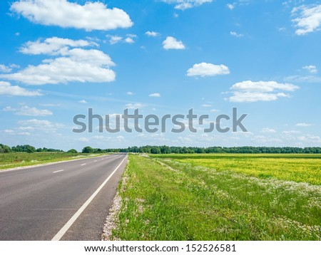 Straight highway through blossoming meadow before forest against blue sky background. Kaluzhsky region, Russia.
