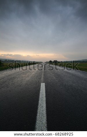 Straight lonely road at sunset after storm