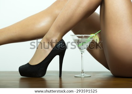 Straight naked sexy female legs in black leather shoes on high heels and cocktail with lime in glass on white background, horizontal picture - stock photo