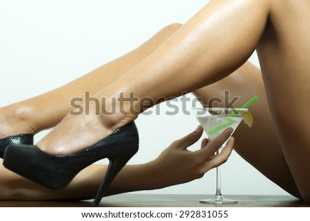Straight naked sexy female legs in black leather shoes on high heels and hand holding cocktail with lime in glass on white background, horizontal picture - stock photo