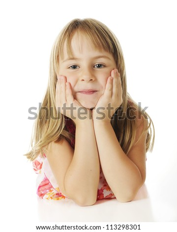 Straight on view of a pretty young elementary girl looking at the viewer while propping her head in her hands.  On a white background.