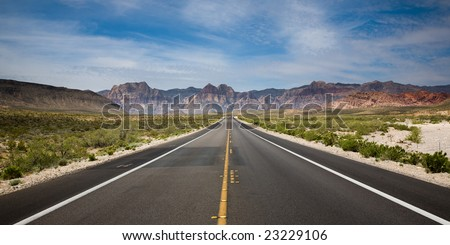 Straight paved road running towards the Red Rock Canyon National Reserve in Nevada, USA with bushes on the sides, hills in the background.