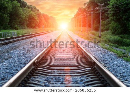 Straight Railroad into orange sunset with clouds in sky - stock photo