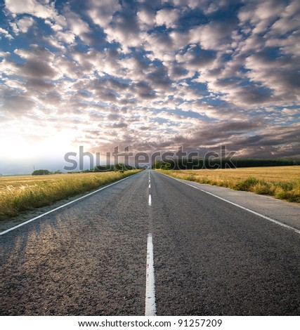 straight road and dramatic sky at the sunset - stock photo