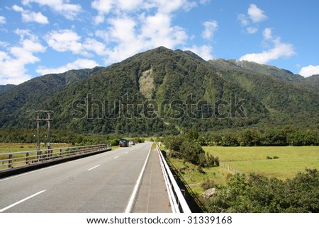 Straight road and mountains in green New Zealand